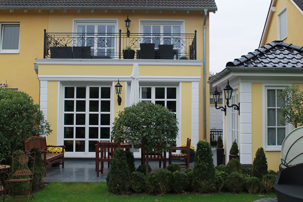Moderne, gelbe Fassade mit Bossensteinen an den Gebäudeecken