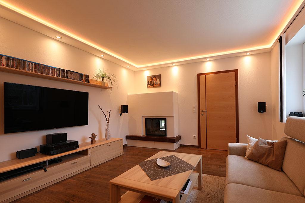 Wohnzimmer mit moderner direkter und indirekter Beleuchtung von Wand und Decke